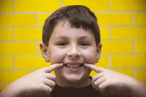 smiling boy pointing at teeth